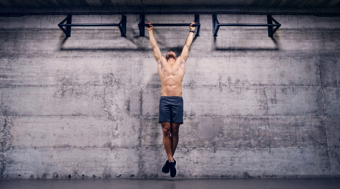 Shirtless man doing pull ups in the gym. When you lose all excuses, you'll find results.